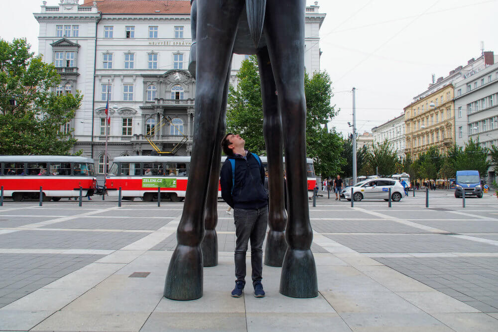 'What's that!': Matt inspects the underside of a horse statue in Brno, Czech Republic