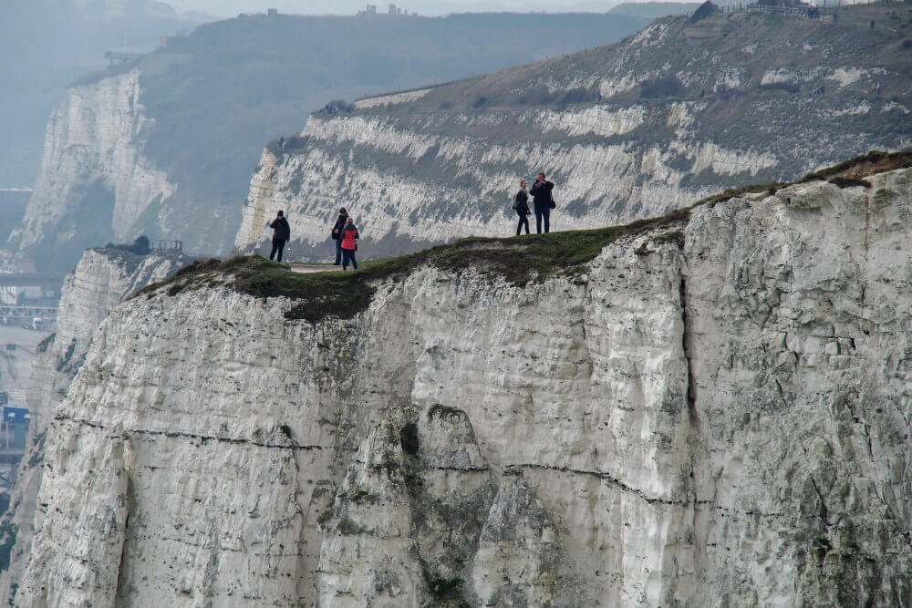 Hikers test the edges of the magnificent White Cliffs of Dover in Kent, UK