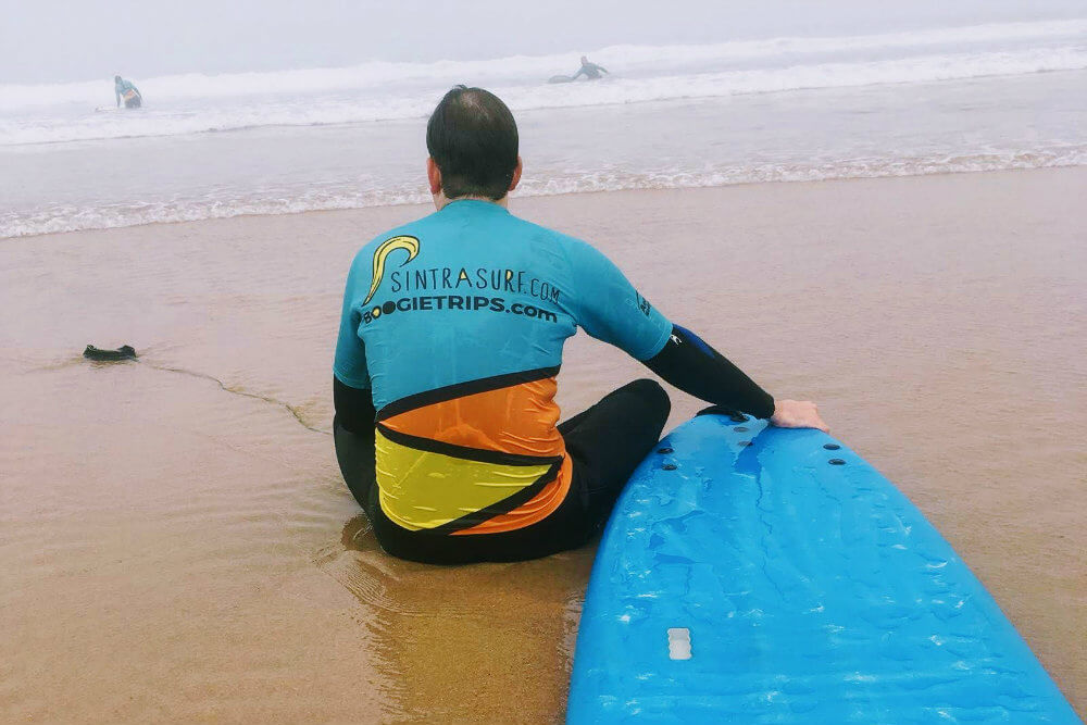Taking a much needed rest between surfing attempts on Praia Grande, Portugal
