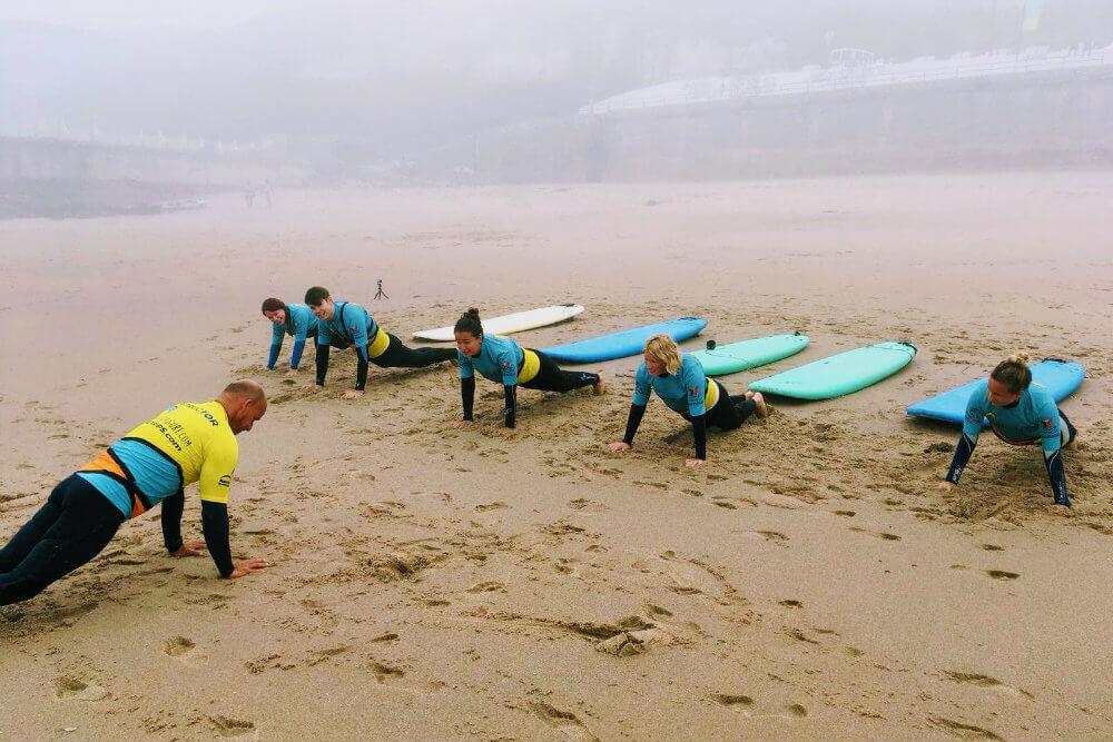 Five trainee surfers warm up on Praia Grande, Portugal