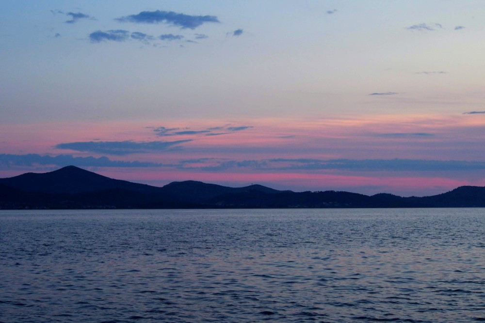 The mountains on a nearby island are silhouetted by the ever changing sky