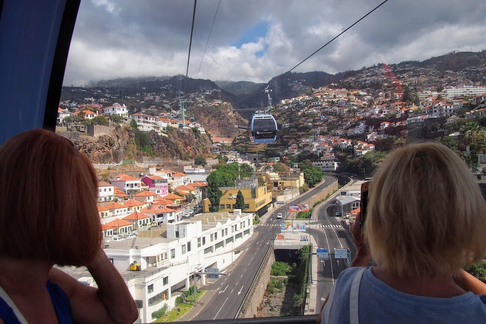 Aboard a gondola, sailing above central Funchal towards Monte