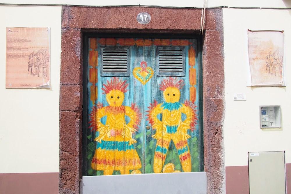 An unusual couple is depicted on a door along Rua de Santa Maria