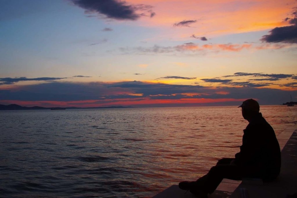 A man sits on the steps of the Sea Organ, quietly contemplating the scene